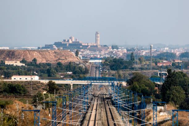 high speed train line and the city of lleida in the background (spain) - lleida zdjęcia i obrazy z banku zdjęć