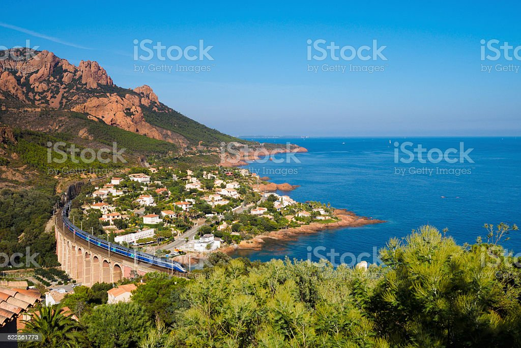 High speed train A high speed train running over a viaduct alongside mediterranean coast. Blue Stock Photo