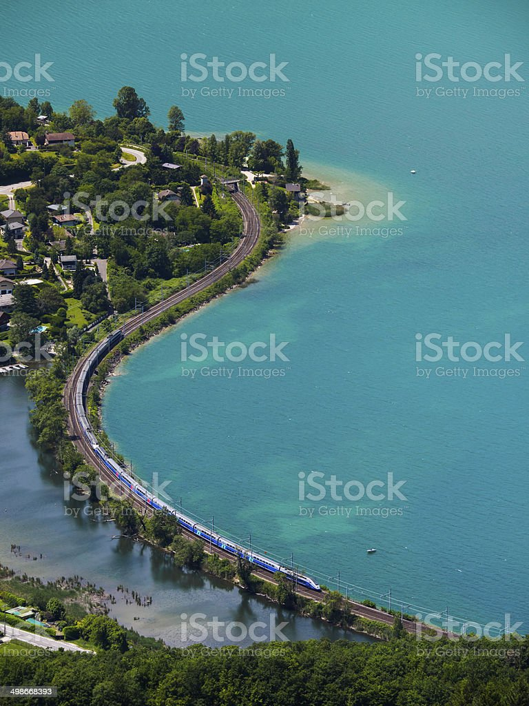 High speed train running aside a lake stock photo