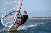 Young man windsurfing with trailing wake. Click to see more...