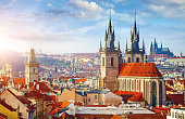 High spires towers of Tyn church in Prague city (Church of Our Lady before Tyn cathedral) urban landscape panorama with red roofs of houses in old town and blue sky with clouds.