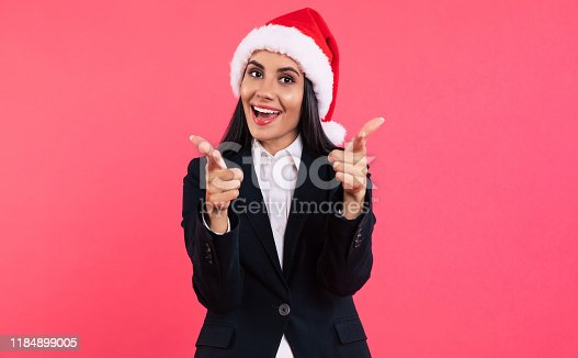 Smartly dressed beautiful woman in Santa hat is posing with finger guns pointing forward, smiling and looking at the camera.