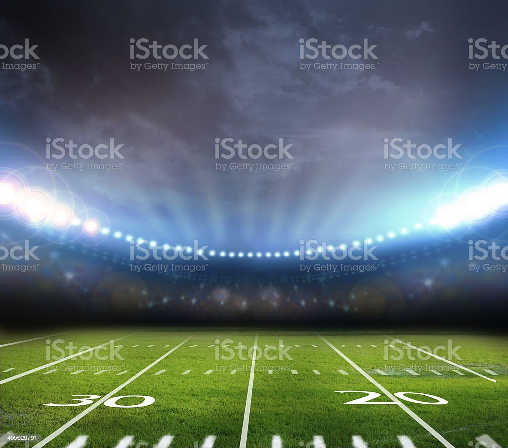 High stadium lights lighting up football field stock photo