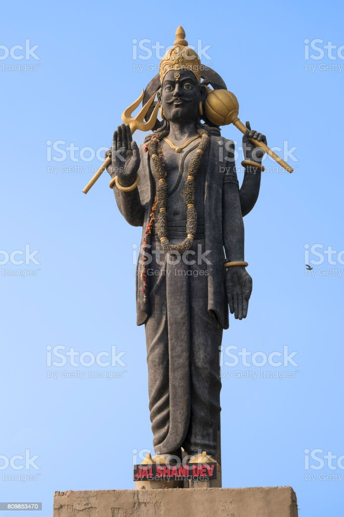 High statue of the Indian deity Shani with raised hand stock photo