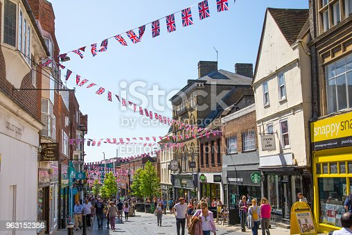 1125782554 istock photo High street of Windsor, decorated with flags and lots of people. tourists making shopping and walking by. England UK. 963152386