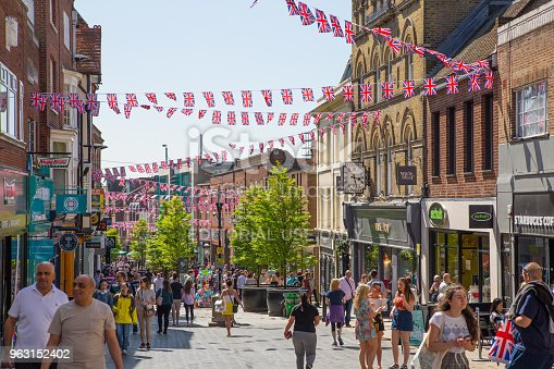 1125782554 istock photo High street of Windsor, decorated with flags and lots of people. tourists making shopping and walking by. England UK. 963152402