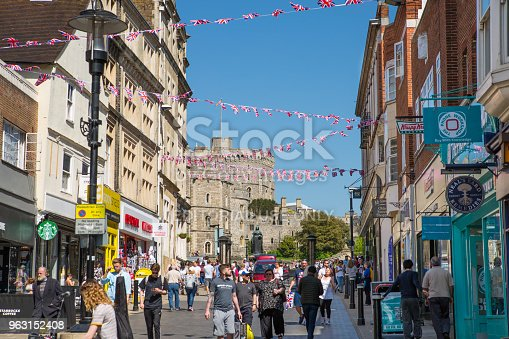 1125782554 istock photo High street of Windsor, decorated with flags and lots of people. tourists making shopping and walking by. England UK. 963152408
