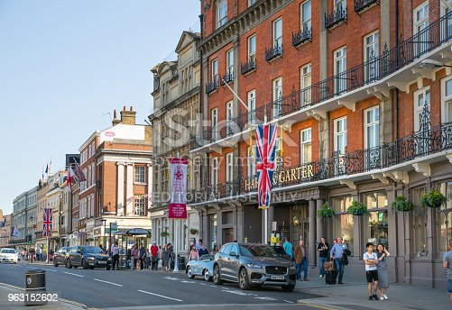 1125782554 istock photo High street of Windsor, decorated with flags and lots of people walking by. England UK. 963152602