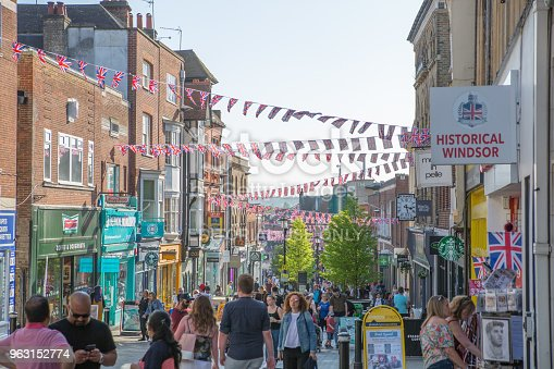 1125782554 istock photo High street of Windsor, decorated with flags and lots of people walking by. England UK. 963152774