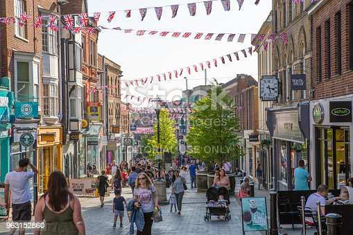 1125782554 istock photo High street of Windsor, decorated with flags and lots of people walking by. England UK. 963152860