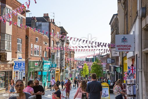 1125782554 istock photo High street of Windsor, decorated with flags and lots of people walking by. England UK. 963152864