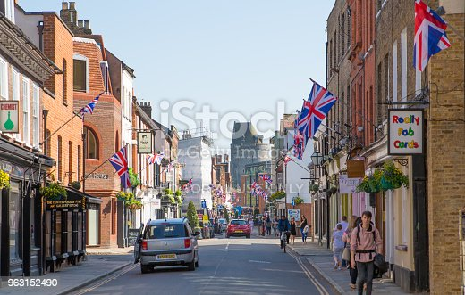 1125782554 istock photo High street of Windsor, decorated with flags and people making shopping and walking by.. England UK. 963152490