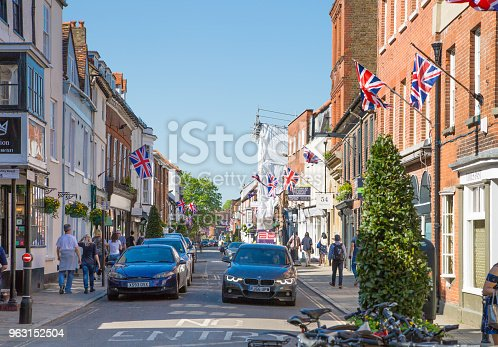 1125782554 istock photo High street of Windsor, decorated with flags and people making shopping and walking by.. England UK. 963152504