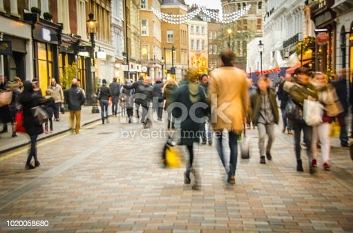 A busy high street scene with a couple holding hands and walking past fashion shops