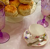 A selection of all butter English Scones with flower patterned Retro China and deep purple glassware