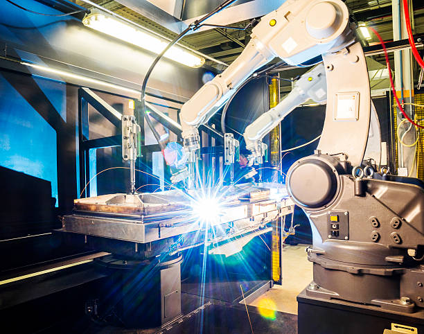 high tech robotic welder in modern metal factory - robotics manufacturing stock photos and pictures