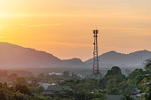 High telecommunication cell tower antenna in asian countryside nature on the background of the silhouettes of the mountains at beautiful orange sunset