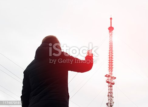 1145453438istockphoto High telecommunication mobile tower from which there is radiation and a man with a mobile phone, poor network, modulation 1174570151