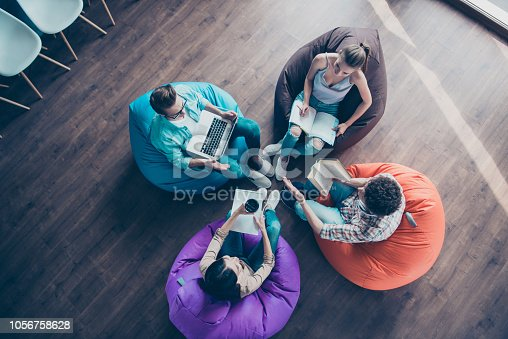 High top angle view of diversity stylish and modern hipster youngster sit in colorful armchairs on the wooden floor work together on the task sit classmates chair bag