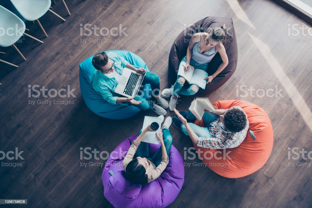 High top angle view of diversity stylish and modern hipster youngster sit in colorful armchairs on the wooden floor work together on the task sit classmates chair bag stock photo