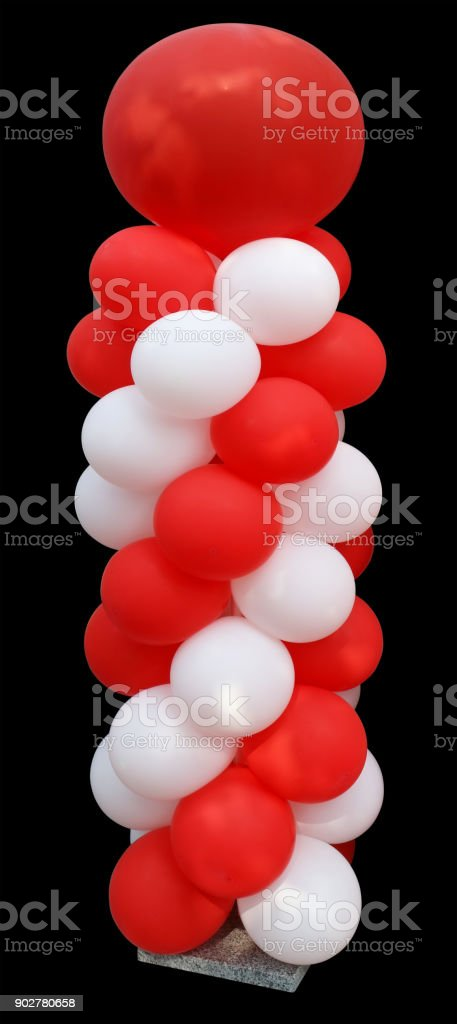 High vertical installation of red and white balloons on a granite stand. Isolated stock photo