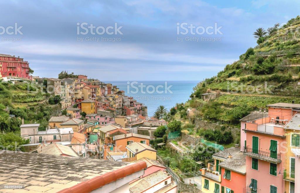 Vila de costa alta vista de Vernazza em Cinque Terre, contra o mar Mediterrâneo, em um dia de verão - foto de acervo
