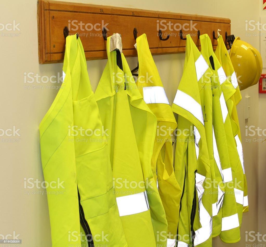 High vis jackets on a coat rack stock photo