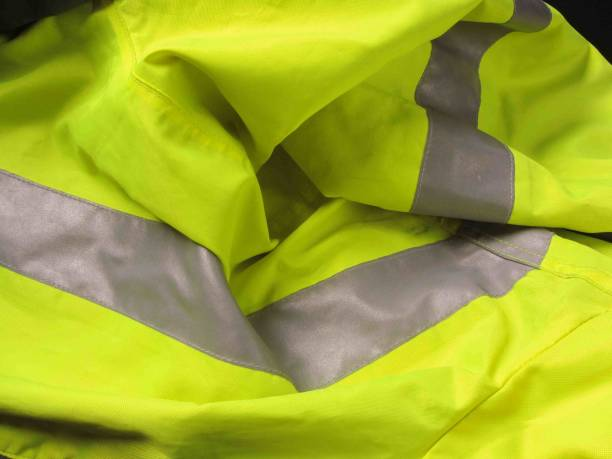 high visibility yellow jacket as background - gilets jaunes photos et images de collection