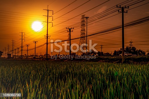High voltage electric pole and transmission lines at sunset time with orange and red sky and clouds. Architecture. Silhouette electricity pylons during sunset. Power and energy. Energy conservation.