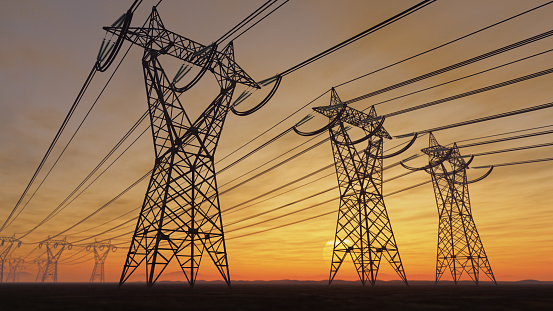 The silhouette of the high voltage power lines during sunset.
