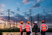 Silhouette high voltage electric tower and engineer team on sunset time and sky on sunset time background.