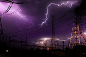 high voltage electrical substation illuminated by lightning flashes during an impending storm at night