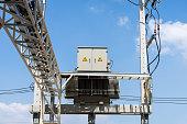 High voltage electrical transformer on concrete pole.