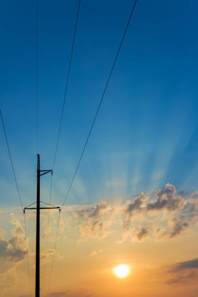 High voltage electricity pylons against beautiful sky with sun rays. Electric pole power lines and clouds. stock photo
