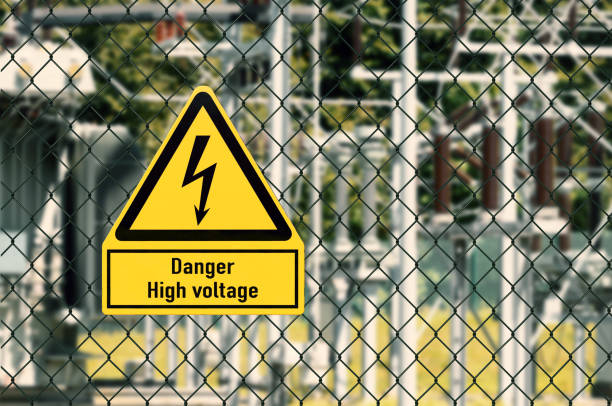 High voltage electricity Symbol Electrical hazard sign placed on a fence of an electrical substation high voltage sign stock pictures, royalty-free photos & images