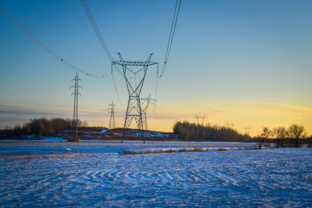 High voltage electricity transmission towers by aerial cables in winter stock photo
