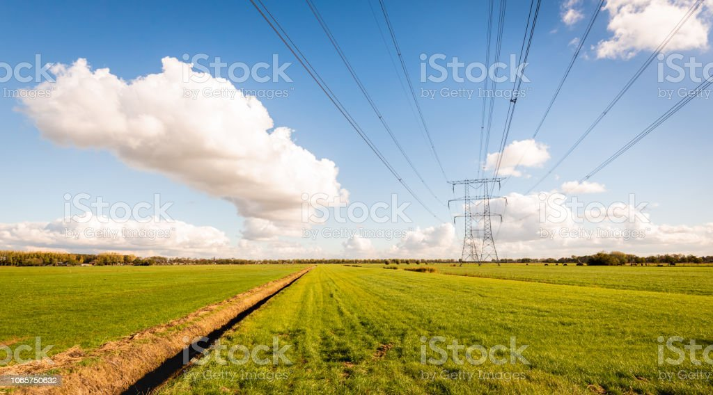 High voltage lines and power pylons in a Dutch agricultural landscape with large meadows stock photo