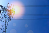 High voltage of electricity pole with cable on clouds blue sky and sun light.