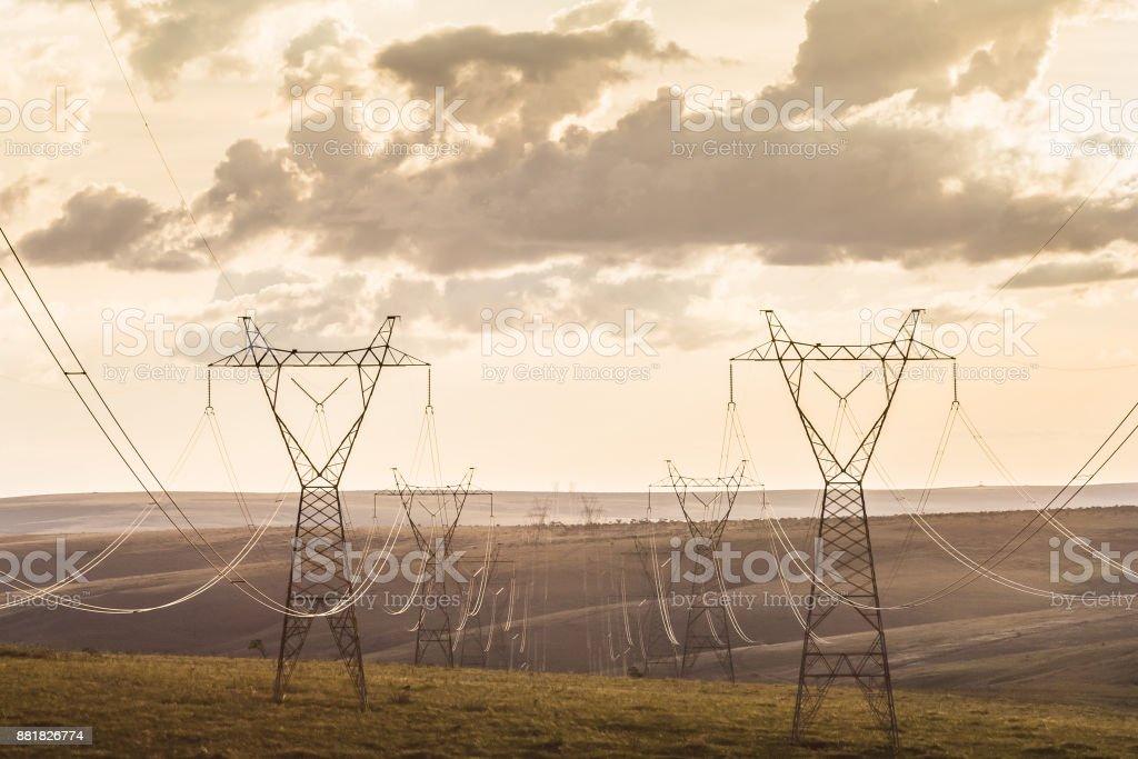 Borne de alta tensão. Linhas de transmissão de alta tensão, ao pôr do sol. - foto de acervo