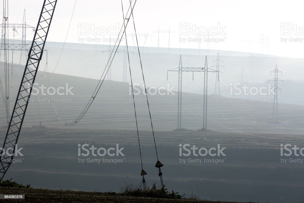 High voltage posts in fog or smog. Concept of the extinct planet and not the ecological energy. royalty-free stock photo