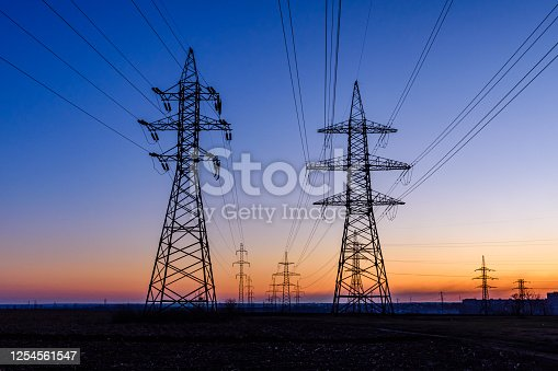 High voltage power line in field at sunset