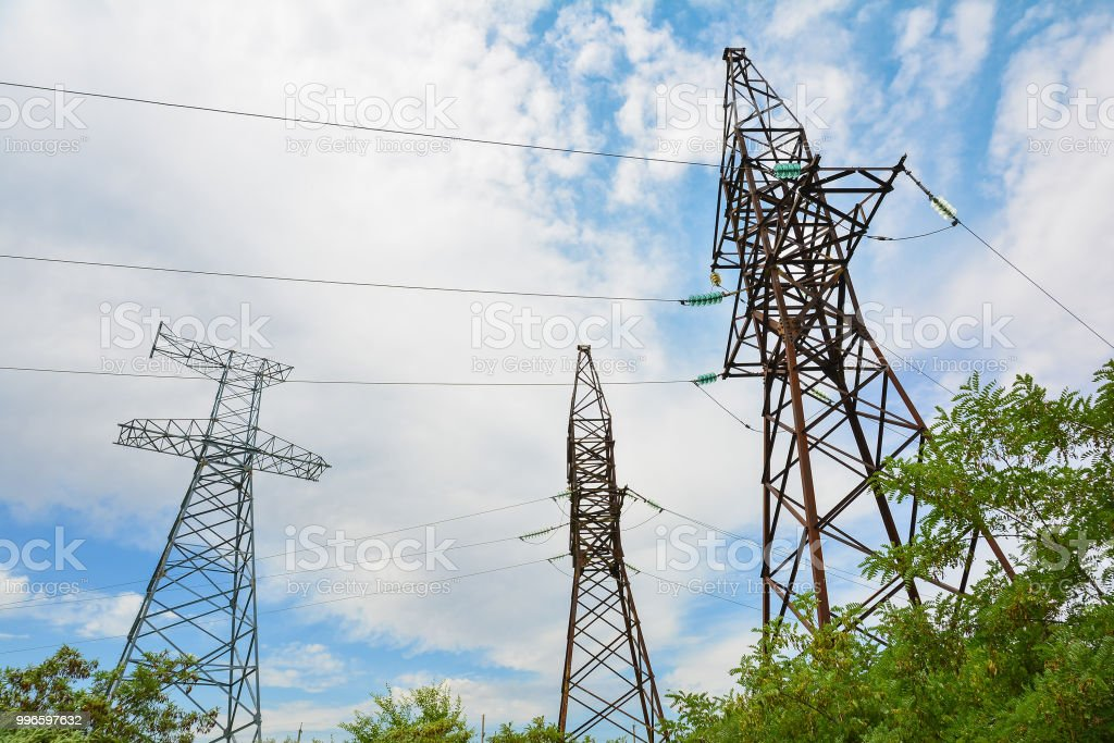 High voltage power lines against the blue sky. Supports of power...