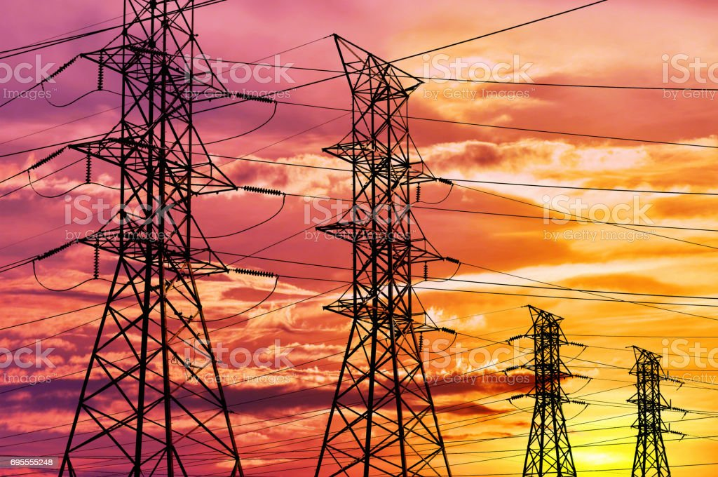 High voltage power lines and pylon towers in a bright sunset stock photo