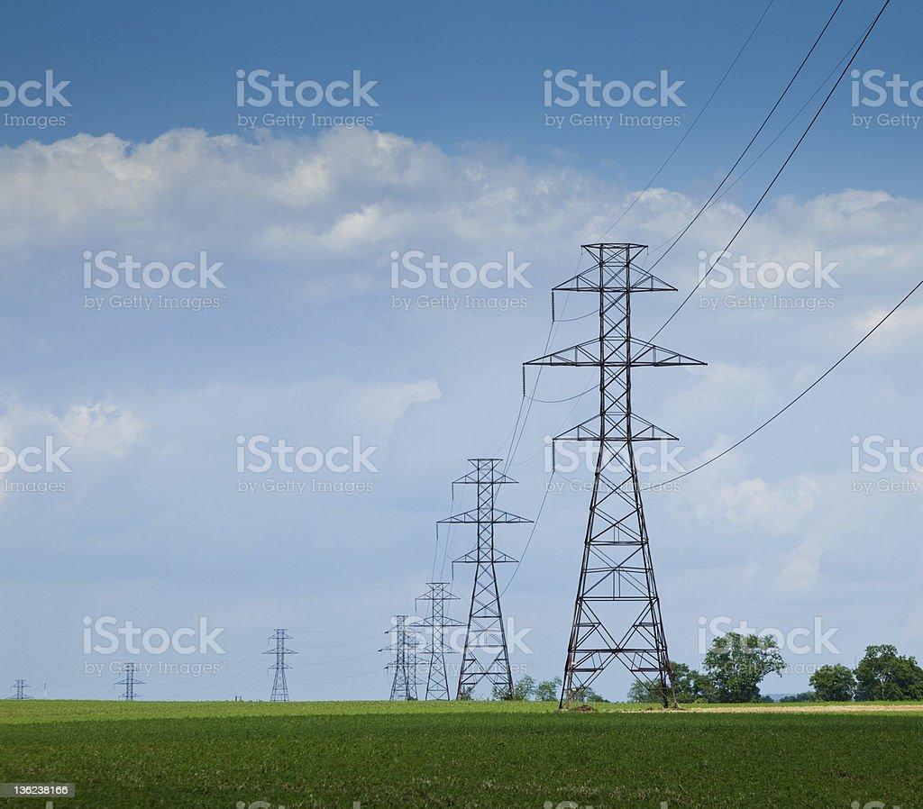 High Voltage Power Lines Through Green Fields stock photo