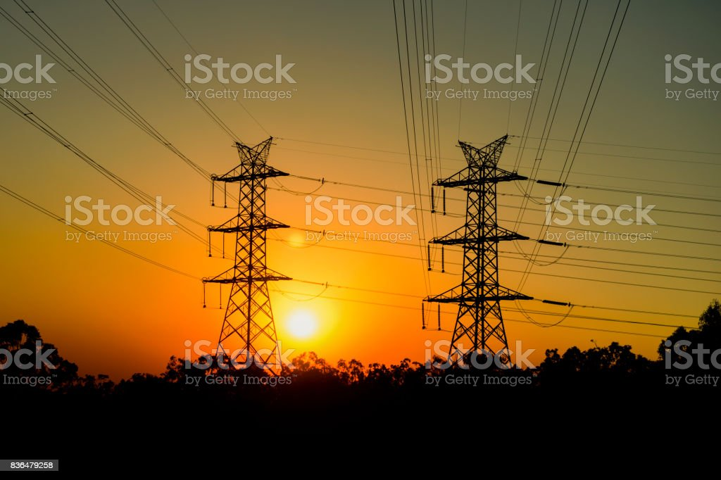 High voltage power tower at sunset stock photo