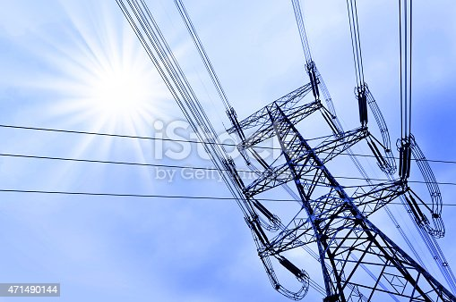 High voltage power tower pylon and line cables, sun and blue sky background