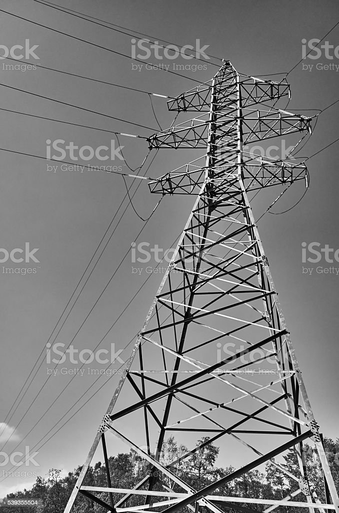High voltage power tower pylon line cables gray sky background stock photo