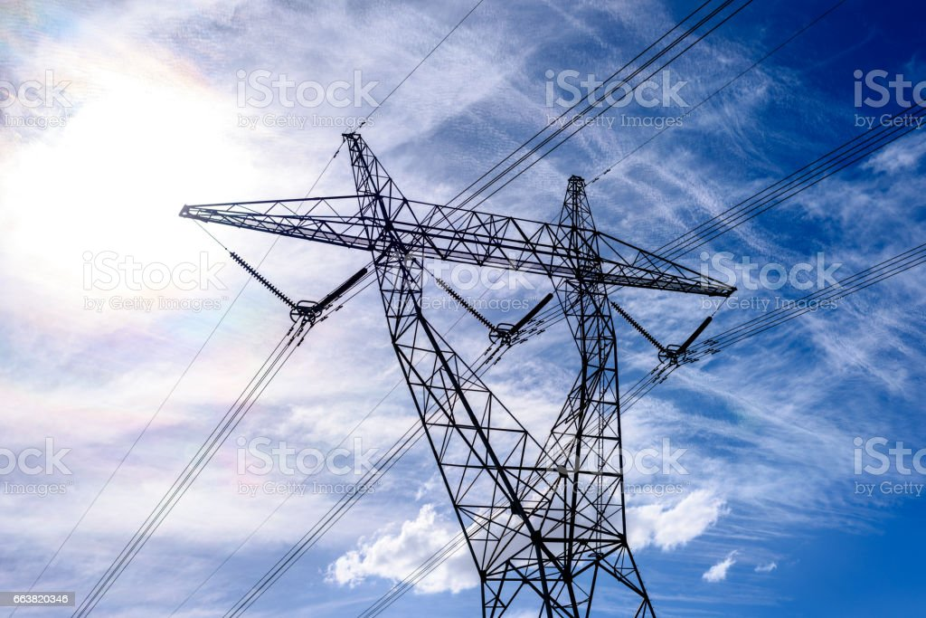 High voltage power transmission tower on blue sky background,  electricity distribution. stock photo