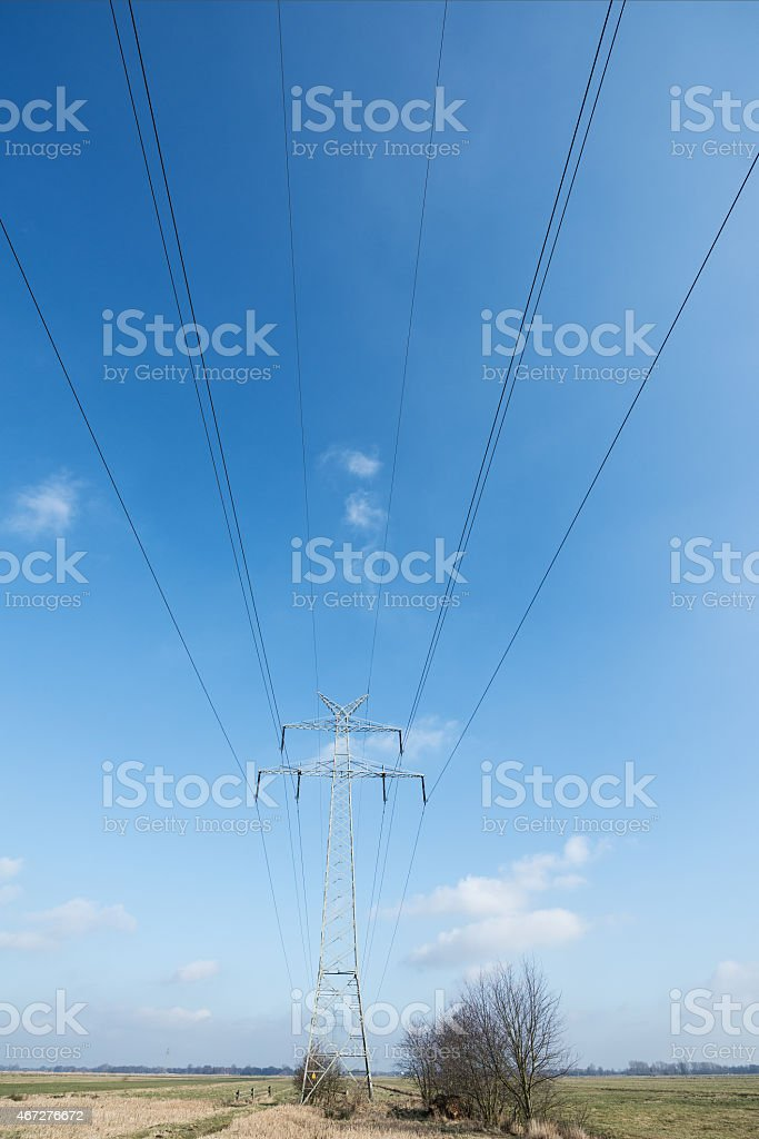 High voltage powerline pylon in front of blue sky stock photo