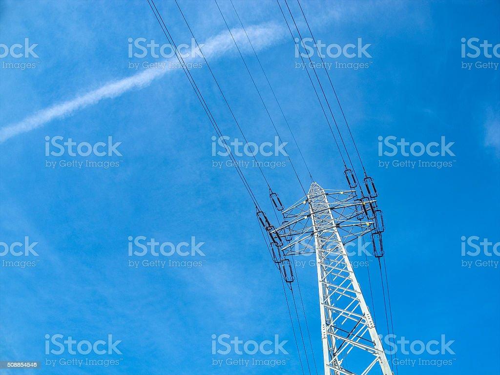 High voltage pylon against blue sky stock photo